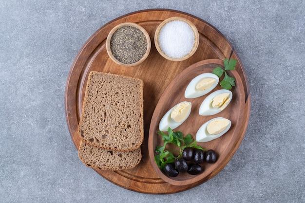 Drewniana deska z gotowanymi jajkami i kromką chleba. wysokiej jakości zdjęcie
