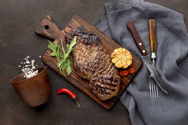 Drewniana deska z grillowanym mięsem i sztućcami