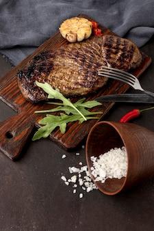 Drewniana deska z grillowanym mięsem na biurku