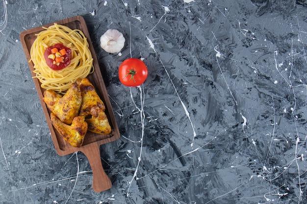 Drewniana deska z makaronem ze smażonymi skrzydełkami z kurczaka na marmurowej powierzchni.