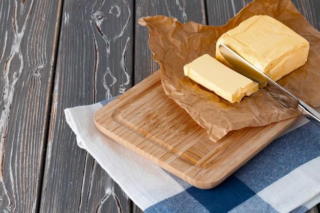 Drewniana deska z masłem na niebieskiej serwetce w kratkę