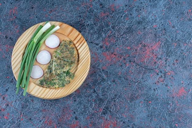 Drewniana deska z omletem z ziołami i zieloną cebulką.