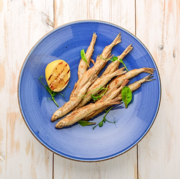 Drewniana deska z pachnącą smażoną rybą i sałatką