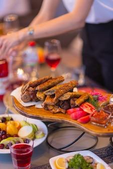 Drewniana deska z pieczonymi na gorąco żeberkami wieprzowymi i kiełbaskami, ozdobiona świeżym majerankiem.