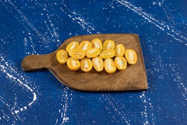 Drewniana deska z pokrojonymi świeżymi owocami kumkwatu na powierzchni marmuru.