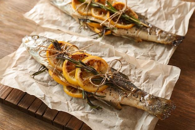 Drewniana deska z pyszną pieczoną rybą na pergaminie