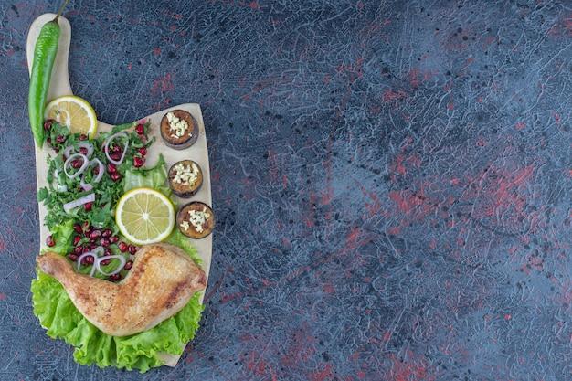 Drewniana deska z pysznym jedzeniem na marmurowej powierzchni.