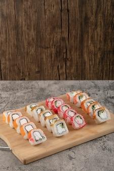 Drewniana deska z różnych rolek sushi na marmurowym stole
