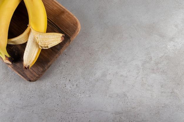 Drewniana deska z soczystym żółtym bananem umieszczona na kamiennym stole.