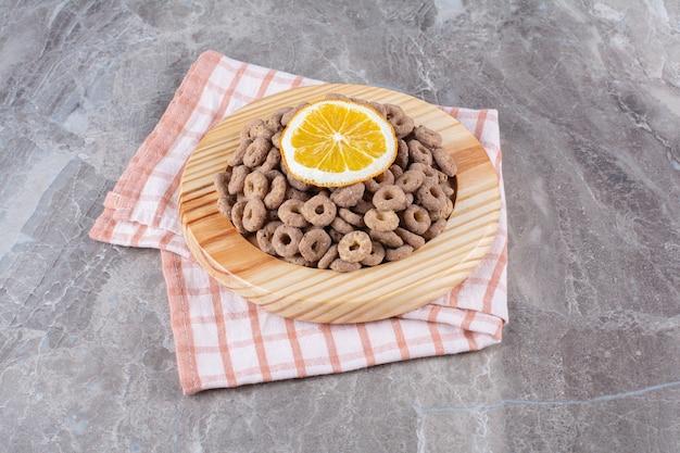 Drewniana deska zdrowych krążków zbóż czekoladowych z plasterkiem pomarańczy.