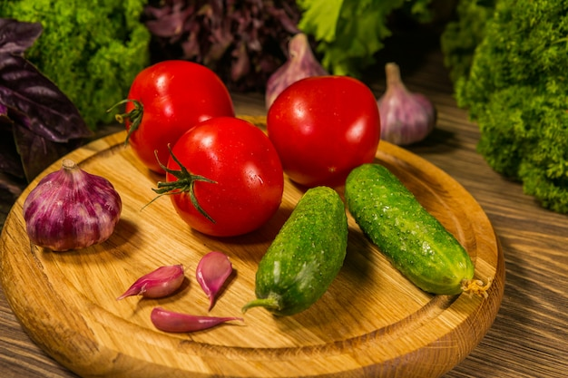 Drewniana deska ze świeżymi pomidorami, ogórkami i czosnkiem. kompozycja ze świeżych warzyw