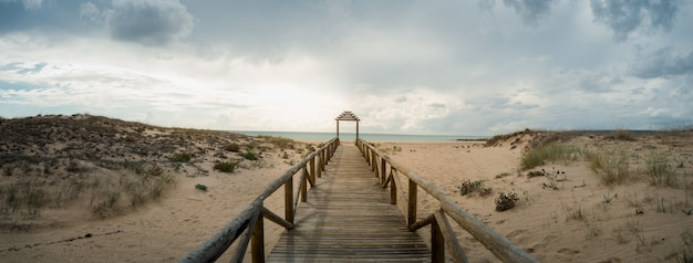 Drewniana długa platforma prowadząca na plażę pod zachmurzonym niebem