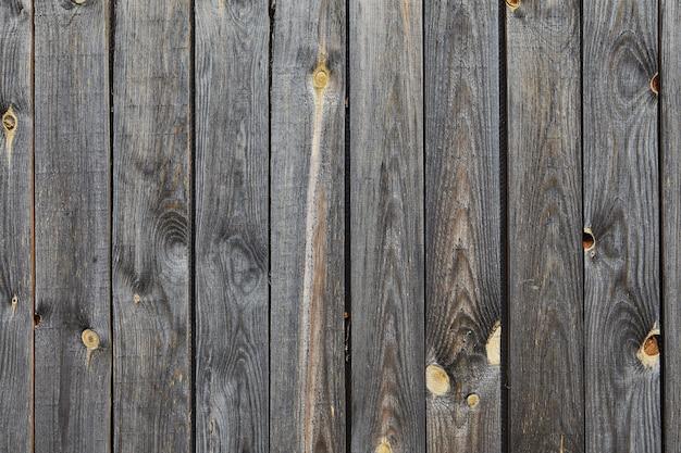 Drewniana faktura ściany starej stodoły z wyblakłych i zwietrzałych szarej sosnowej deski z wiązaną powierzchnią, abstrakcyjna.