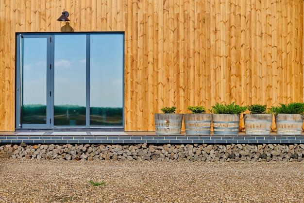 Drewniana fasada drewnianego domu. żółte drewniane deski. okna panoramiczne. doskonałe odbicie widoku w oknie błękitnego nieba.