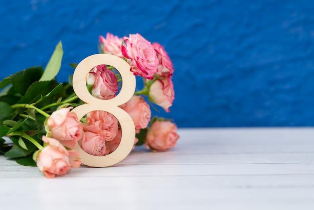 Drewniana figura 8 z różowymi kwiatami na białym stole. międzynarodowy dzień kobiet. 8 marca