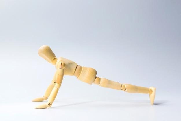 Drewniana figura lalka z push up dla zdrowia na białym do treningu fizycznego