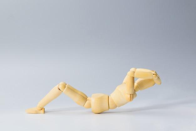 Drewniana figura lalka z siedzieć na zdrowie na białym do ćwiczeń