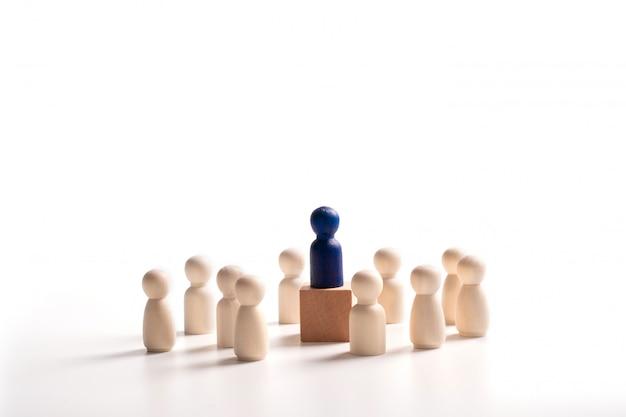 Drewniana figura stojąca na pudełku dla pokazania wpływu i wzmocnienia. koncepcja przywództwa biznesowego dla zespołu liderów