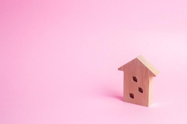 Drewniana figura z wielopiętrowym domem na różowym tle. trzypiętrowy dom.
