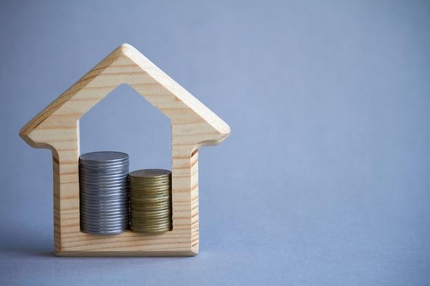 Drewniana figurka domu i dwie kolumny monet wewnątrz na szaro