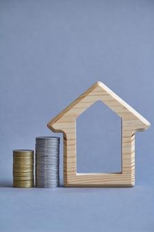 Drewniana figurka domu z dwiema kolumnami monet w pobliżu na szarym tle.