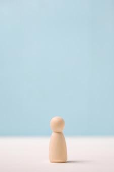 Drewniana figurka na niebieskim tle. pojęcie samotności.