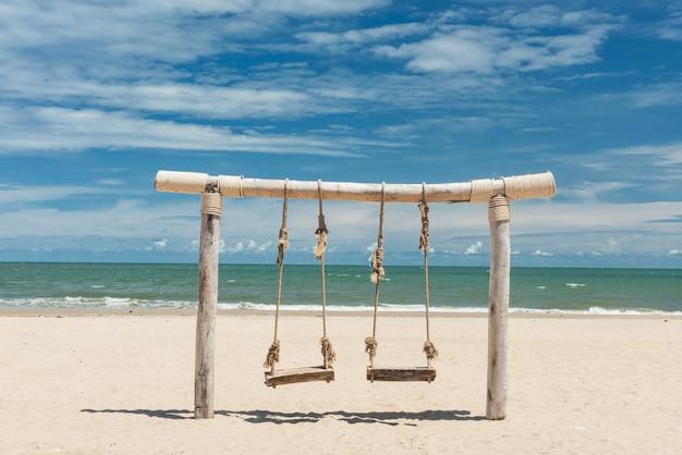 Drewniana huśtawka linowa na białym piasku na tle morza i błękitnego nieba latem na plaży cha-am, petchaburi, thaialnd. wakacje w tropikach. miejsce na relaks i orzeźwienie w świeżej atmosferze.