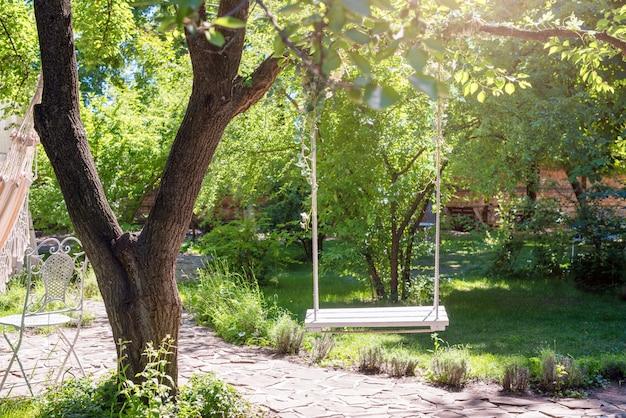 Drewniana huśtawka na linach pod dużym drzewem w ogródzie.