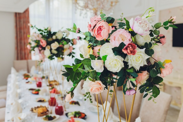 Drewniana huśtawka ozdobiona sztucznymi kwiatami.