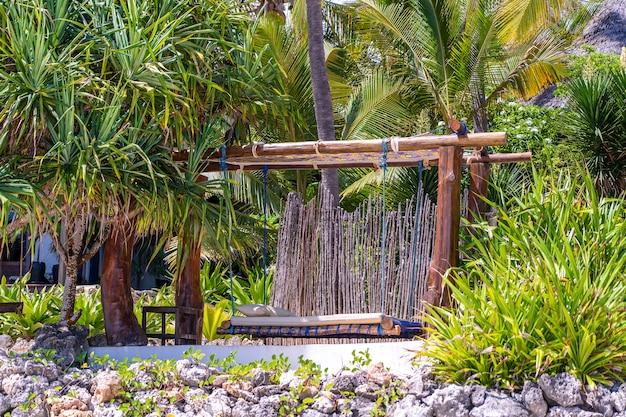 Drewniana huśtawka pod baldachimem na tropikalnym plażowym pobliskim morzu, wyspa zanzibar, tanzania, afryka wschodnia