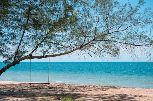 Drewniana huśtawka wisząca na drzewie na plaży w tropikalnym morzu. wakacje na koncepcji lato