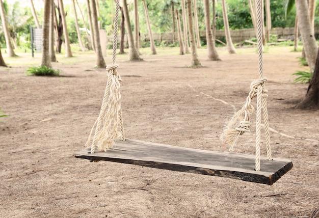 Drewniana huśtawka z liny w parku