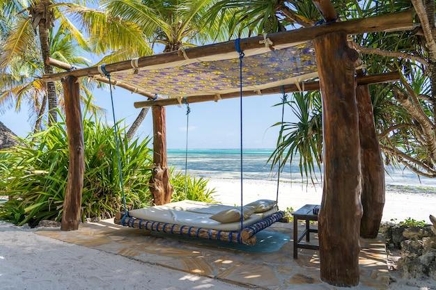 Drewniana huśtawka z materacem i poduszkami pod baldachimem na tropikalnej plaży w pobliżu morza, wyspa zanzibar, tanzania, afryka wschodnia, koncepcja podróży i wakacji