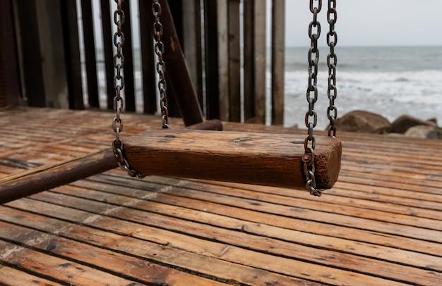 Drewniana huśtawka z metalowymi łańcuchami na tle morza bałtyckiego.
