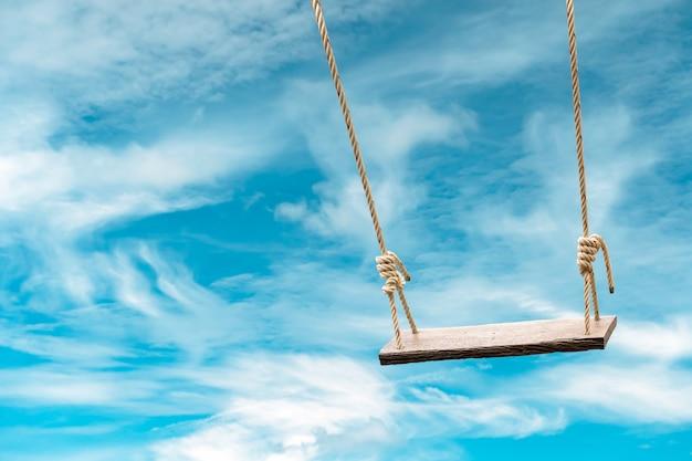 Drewniana huśtawka z pastelowym niebieskim niebem i chmurą