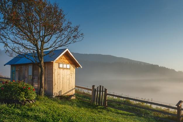 Drewniana kabina z ogrodzeniem i drzewem na odgórnym og wzgórzu w wschodzie słońca. góry