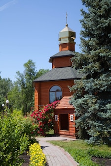 Drewniana kaplica w parku miejskim. kwitnące krzewy róż i różnych krzewów