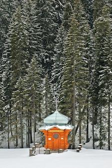 Drewniana kaplica w zaśnieżonym lesie ukraińskie karpaty podnóża goverla