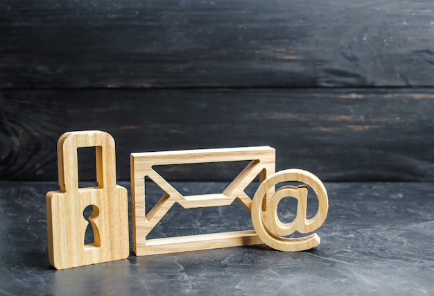 Drewniana kłódka stoi obok koperty e-mail.