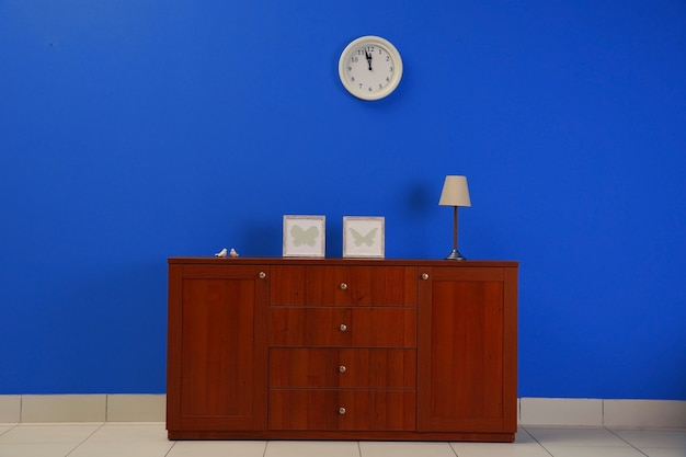 Drewniana komoda na niebieskim tle ściany