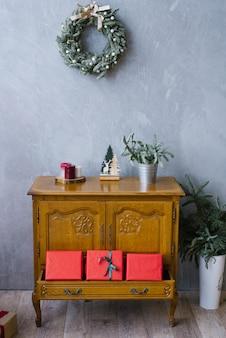 Drewniana komoda z czerwonymi pudełkami prezentowymi i świątecznym wieńcem na ścianie w salonie