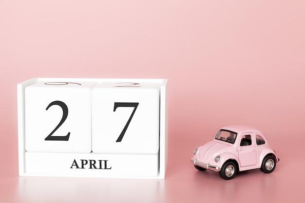 Drewniana kostka z bliska 27 kwietnia. dzień 27 kwietnia miesiąca, kalendarz na różowo z retro samochodem.