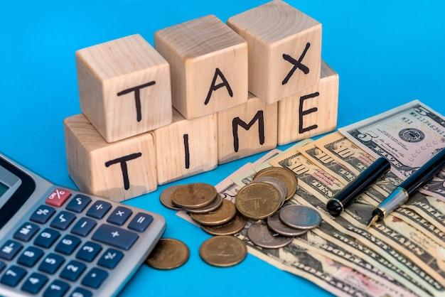 Drewniana kostka z czasem podatku tex i dolara nad monetą na niebieskim tle
