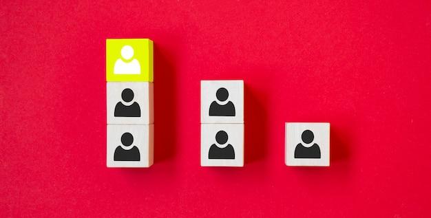 Drewniana kostka z ikoną osoby wyróżnia się z tłumu na czerwonym tle. zdanie odrębne, rozbieżne poglądy i różne koncepcje