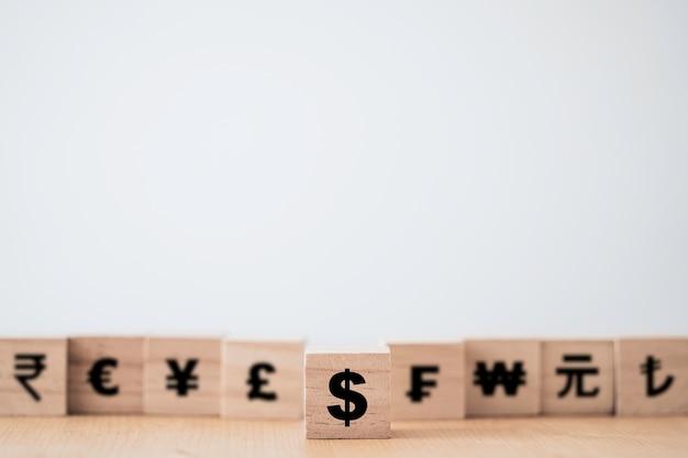 Drewniana kostka ze znakiem dolara amerykańskiego wyróżniająca się od innych walut yuan yen, euro i funt szterling. dolar amerykański jest główną i popularną walutą wymiany na świecie. koncepcja inwestycji i oszczędzania.