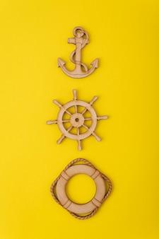 Drewniana kotwica, kierownica i koło ratunkowe na żółtym tle.