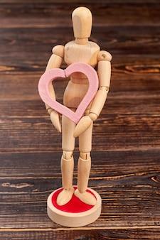Drewniana kukiełka trzyma różowe serce. drewniana osoba posiadająca piękne ozdobne serce. pojęcie miłości i romansu.