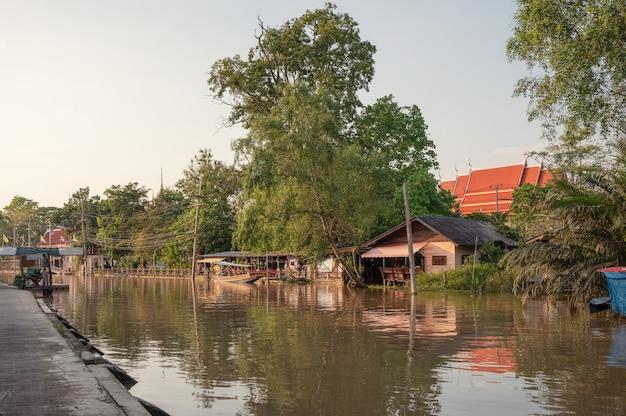 Drewniana kwatera rodzinna unosząca się nad rzeką i wieczorem świątynia w amphawa, ratchaburi