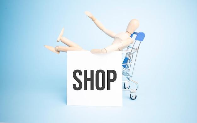 Drewniana lalka w zakupach z białym papierem i znakiem sklepu. pomysł na biznes