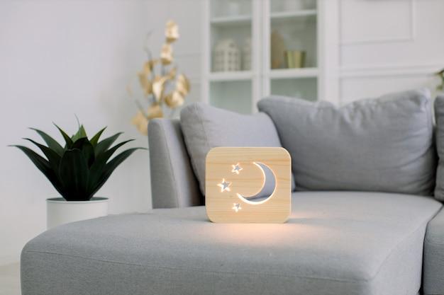 Drewniana lampka nocna z obrazem księżyca i gwiazd, na szarej sofie, w stylowym jasnym wnętrzu salonu